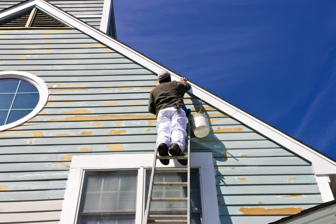 paint contractor on a ladder working on painting the exterior of a home