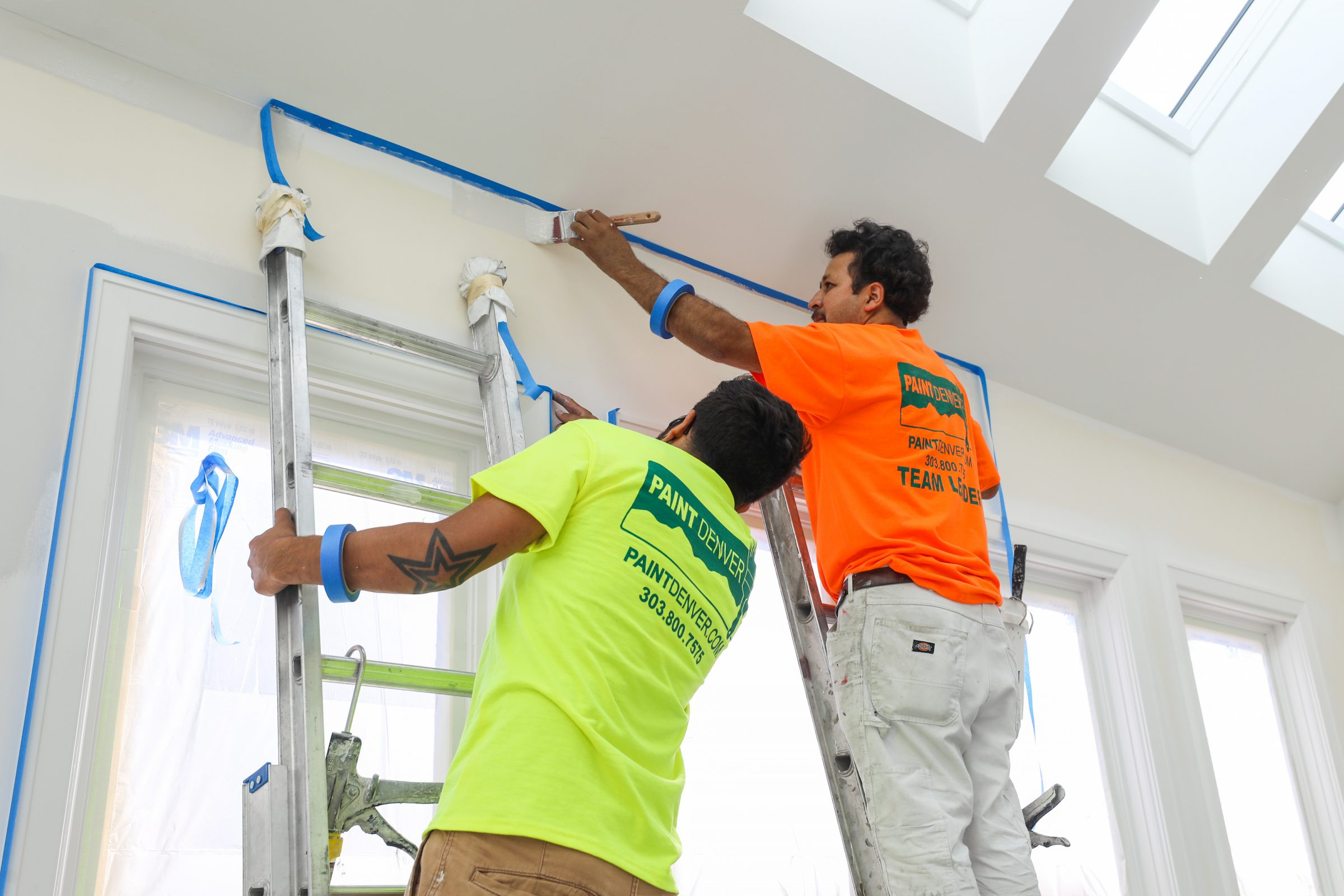 two men prep a the interior of a home to be painted with primer